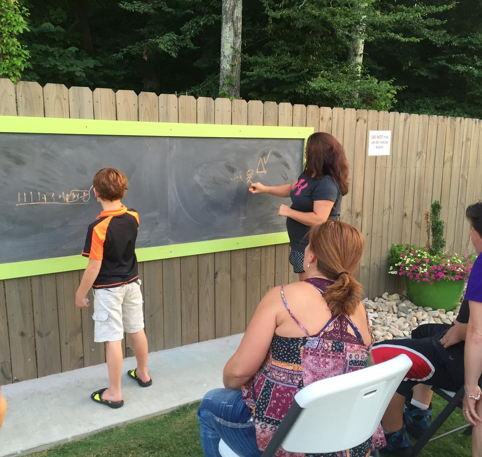 People writing on an outdoor chalkboard.