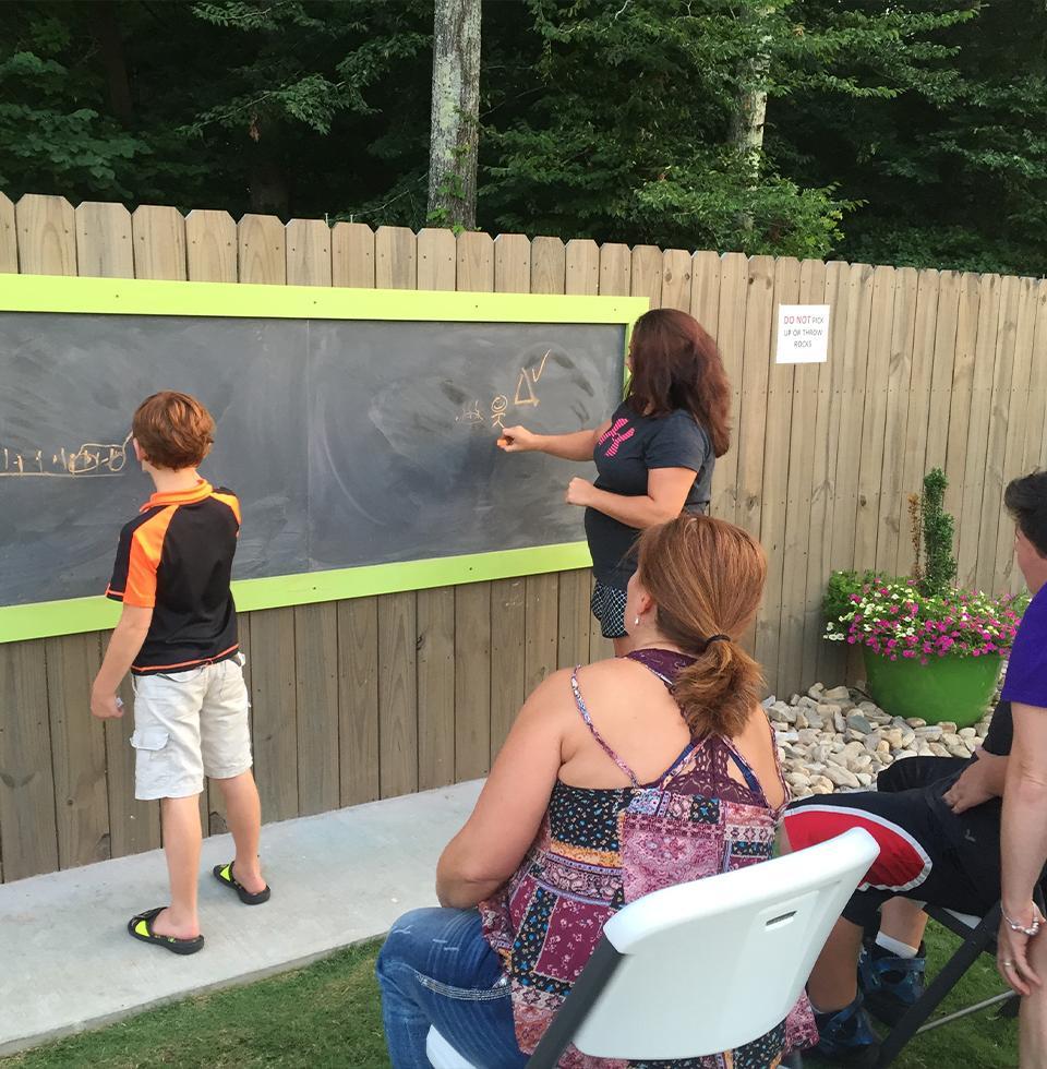 People writing on an outdoor chalkboard.