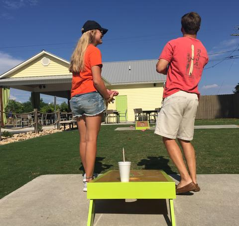 Two adults playing corn hole.
